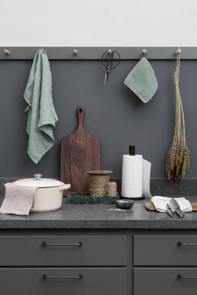 Beautiful simple kitchen styling, dark units and worktops, and pegs to display utensils