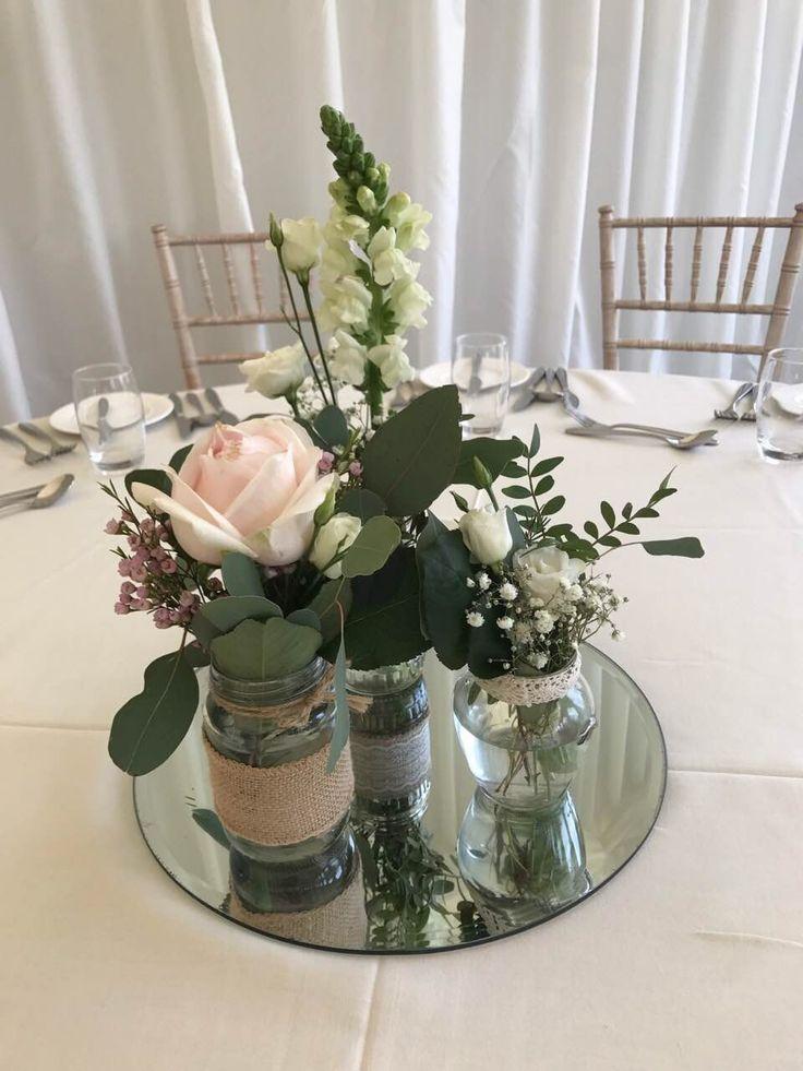 Jam Jar Arrangement: Eucalyptus, Lisianthus, Gypsophila, Sweet Avalanche, Soft Pink Wax Flower on a mirrored plate.