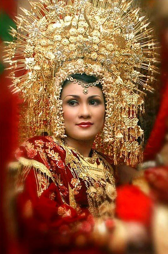 """Indonesian wedding headdress and costume showing the """"suntiang"""" a tradional headpiece with many layers of metal flowers"""
