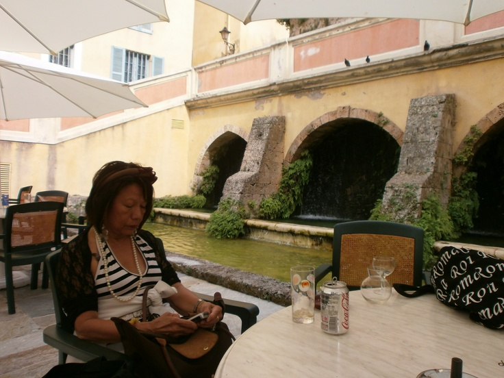 Adelina is shown here relaxing in the Place de l'Evêché in the very heart of the historic centre of Grasse. The water in the fountain arrives from the torrent 'La Foux' which has been essential to the city's wellbeing and development since its foundation in the Xth century.