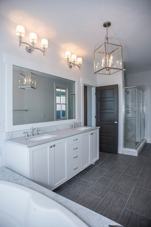 white ensuite, grey marble bath surround and countertops, double vanity, polished nickel fixtures & pendant, dark toned wood effect offset tile floors, large framed mirror, glass shower