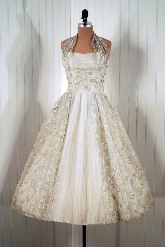Wedding or Formal Gown: 1950's, fully-lined net/tulle embellished with heavily-embroidered floral detailing and halter, pleated skirt in middle vent.    *  *Cocktail-Length Middle-Pleated