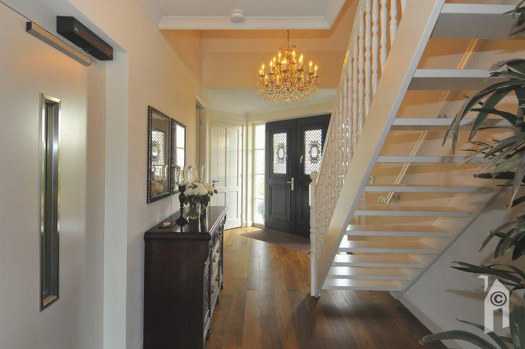 Na de entree zien we een houten trap naar de verdieping en rechtdoor kom je strikt genomen weer bij het licht van de tuindeuren uit.