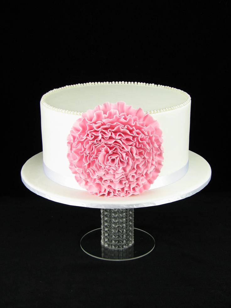 White chocolate mud cake with raspberries and filled with white chocolate ganache. The cake is covered in fondant with a large fondant ruffle flower and a row of edible pearls around the top.