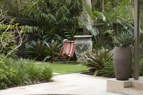 Add an appropriately scaled architectural element. Large palm leaves and other tropical plants could eat up most garden statues like a Venus flytrap gobbles insects. This urn's simple shape does not distract from the shapes of the lush and exotic plants.