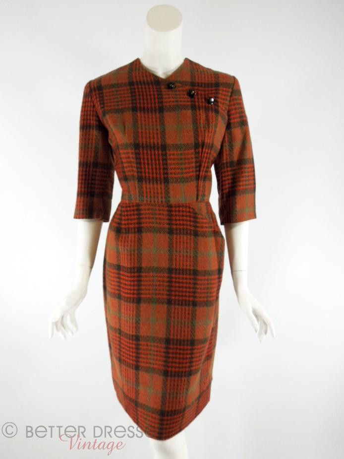 Brown, orange, greenish gray and black plaid wiggle sheath dress from the 1950s. Shallow V-neck extends diagonally with three decorative buttons covering snap closure. Over-elbow sleeves. Beautifully