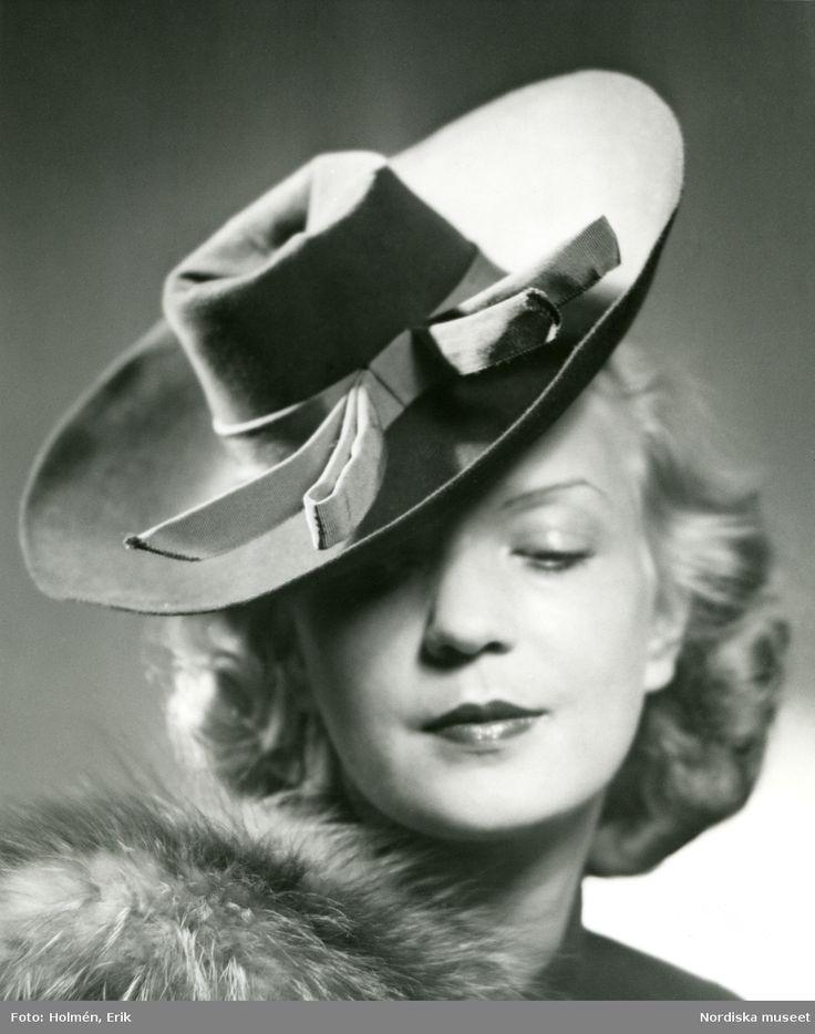 1940. Porträtt av kvinna klädd i päls och hatt med ljust band. Foto: Erik Holmén