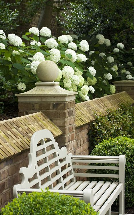 Love! The Lutyens-style bench contrasting crisply with the mellow brick wall, the bright hydrangeas reflecting back the white... lovely!!