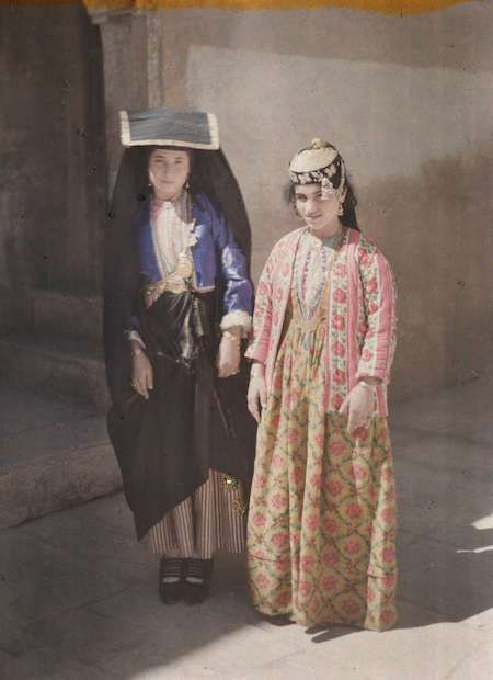 """Iraq: Two young women, noted by Frédéric Gadmer as """"Christians,"""" pose on a Mosul street in 1927.Autochrome photography from Archives of the Planet; a project conceived and financed by French banker Albert Kahn in 1909."""