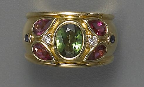 A gem-set, diamond and eighteen karat gold ring, French, Cartier  the wide polished gold band centering an oval-shaped green tourmaline flanked by two pear-shaped pink tourmaline and accented by round cabochon sapphires and round brilliant-cut diamonds; signed Cartier, no. 88173; with French assay marks.