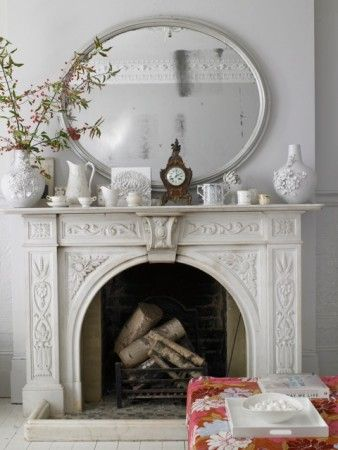 Kind of over french country.... but this is really fresh...love the ornate fireplace, the circular mirror and all the white