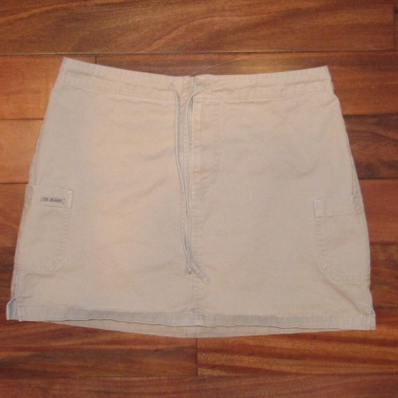 Calvin Klein Jeans light khaki mini skirt Size 8. Light khaki. Zipper, button and drawstring closure. Two side pockets with velcro closure. Waist (laid flat) measures 16 inches and length measures 15 inches. 100% cotton and in excellent condition. Feel free to ask me any questions😊 Calvin Klein Skirts Mini