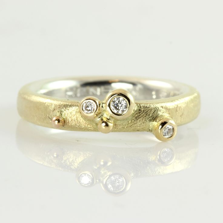 Diamond ring with bubbles and 2 layers of gold. The ring of 14k gold hides a little surprise because it has a lining of white gold, which only becomes visible when it is removed. These double-layer rings have become something of a classic and come in many different combinations. A bunch of shiny bubbles loosen the strict lines and the rough surface of the ring and some of them carry a sparkling diamond. See more double-layered rings here