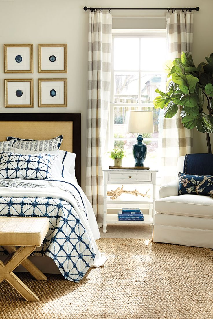 Chic, summer bedroom with shibori bedding, indigo accents, and raffia X-benches.