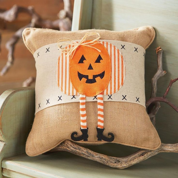 If you're looking to add a touch of Halloween whimsy to your home, then this pumpkin pillow by Mud Pie would be perfect. Featuring a cross-stitched fabric band and a smiling Jack O' Lantern applique w