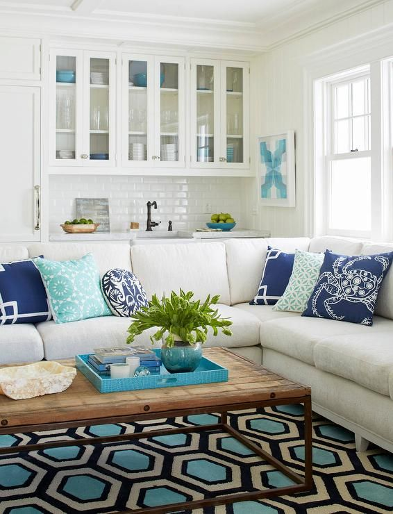 Gorgeous beach style living room with blue accents features white glass front bar cabinets fixed above white beveled subway backsplash tiles located behind a bronze vintage faucet paired with a small apron sink.