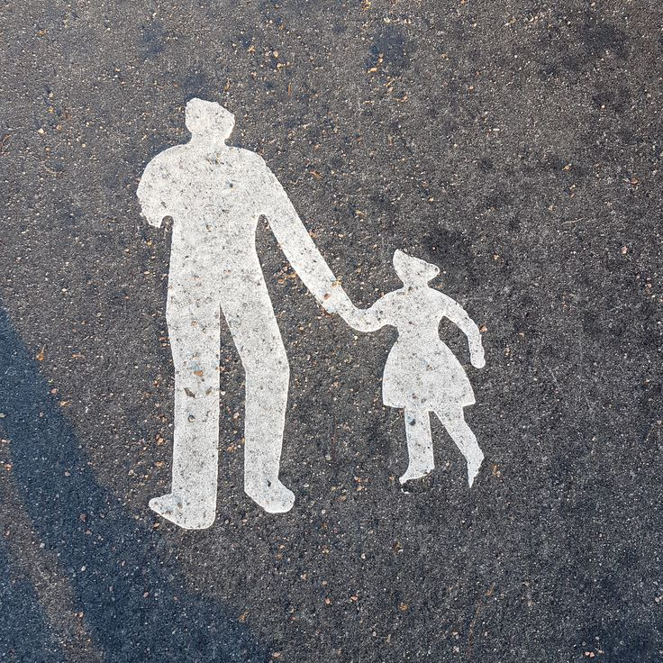 This worn down pedestrian sign suddenly became a happy zombie family!