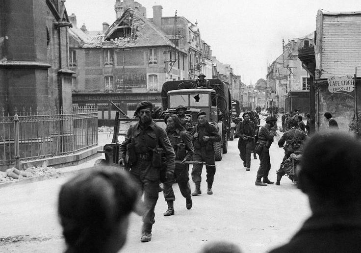 Following the initial landings on the French coast, Allied troops at once began to push inland. Passing through Normandy villages they were given warm welcome by the inhabitants. British Commandos passing through the streets of a town near Caen on June 6, 1944.