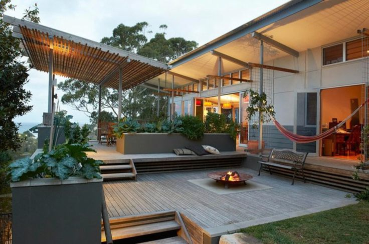 terrasse sur terrain en pente en bois composite, foyer extérieur, banquette en bois et coussins décoratifs