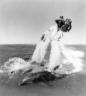 Artwork of George Clinton riding on the back of a pair of dolphins while dressed as a cowboy which was used to publicise Parliament's 1978 album Motor Booty Affair