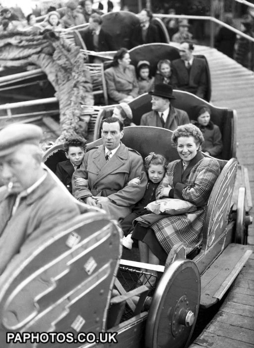 A family on the 'Caterpillar' ride at the Festival of Britain fun fair at Battersea Park. 1951