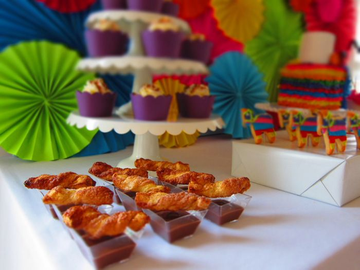 Mexican Fiesta!  I love everything about this party: the bright backdrop, dulce de leche cupcakes, churros con chocolate and the festive ruffled cake.