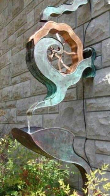Évacuation fantaisie   de gouttières  en cuivre sur mur de pierres