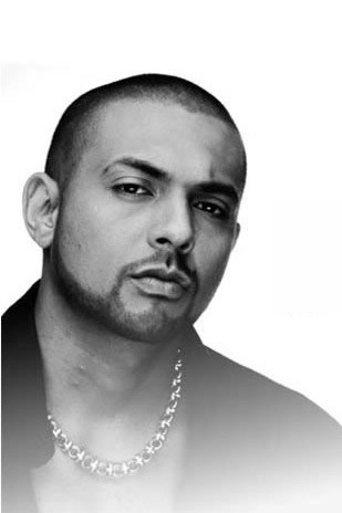 """Sean Paul (born Sean Paul Ryan Francis Henriques), Jamaican Grammy-winning dancehall and reggae artist. His biggest hits included Get Busy, Like Glue, Gimme the Light, I'm Still in Love with You, Ever Blazin', (When You Gonna) Give It Up To Me, We Be Burnin', Temperature, Never Gonna Be The Same, Got 2 Luv U and She Doesn't Mind. He also appeared on Beyonce's megahit, Baby Boy. Because of his mixed heritage, some consider him a personification of the Jamaican Motto """"Out of Many, One People""""."""
