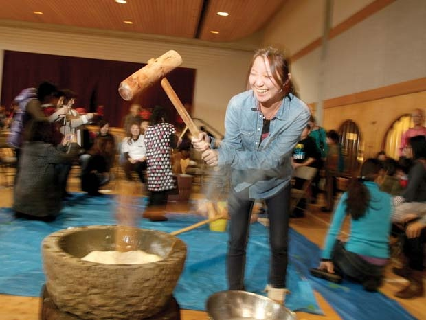 Hit it:  Kaoru Nakakuma pounds glutinous rice into a paste - part of the process for making mochi, traditional Japanese rice cakes - at the Nikkei Centre's annual year end celebration.