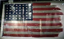 The flags from the first and second flag-raisings are conserved in the National Museum of the Marine Corps. The second flag, pictured here, was damaged by the high winds at the peak of Suribachi. Like all American flags during World War II, it has 48 stars, since Alaska and Hawaii were not yet U.S. states.