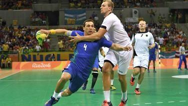 Deutschlands Handballer Julius Kühn (r.) foult Brasiliens Joao da Silva.
