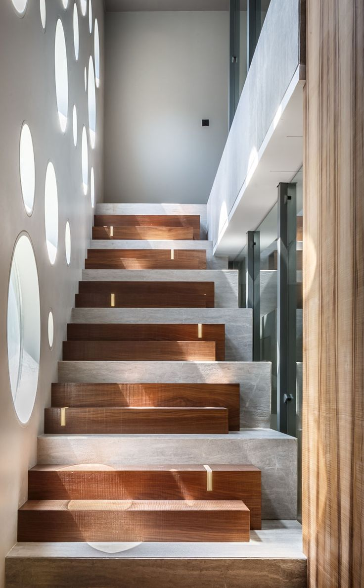 The design of these stairs combines wooden steps with a concrete base, and LED strips add some discreet lighting.