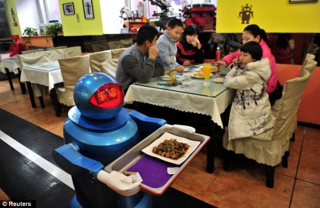 A robot delivers a dish to hungry diners at Robot Restaurant where 20 robots are used to deliver and cook food as well as usher customers and entertain them, China