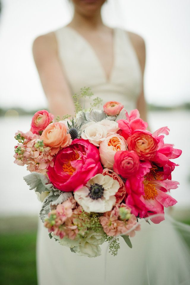 close up of vibrant bridal bouquet of coral charm peony, white anemone, peach stock, peach juliet garden rose, peach ranunculus, pink ranunculus, thistle, white majolik spray rose, lamb's ear dusty miller and seeded eucalyptus.