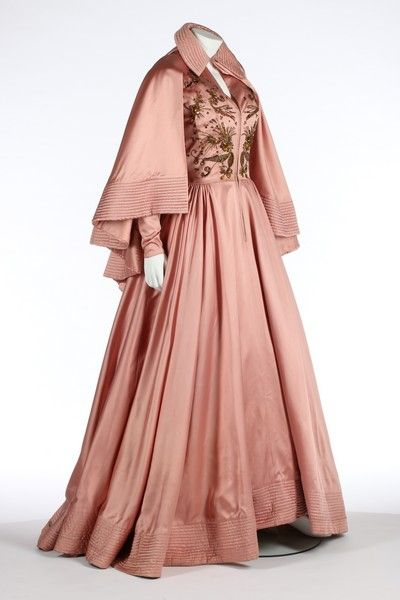 An early Jacques Fath ball gown and matching cape, probably Spring-Summer, 1948. the gown labelled 'Jacques Fath, Paris', of deep rose-pink satin, zip-fastened centre-front and with zips to both cuffs, the bodice embroidered with stylised flowers and seeds, large elliptical topaz coloured pastes, chunky beads and raised couched threads and braids and scattered silver and gold sequins See more at: http://kerrytaylorauctions.com/one-item/?id=81auctionid=401#sthash.KlIZkgw3.dpuf