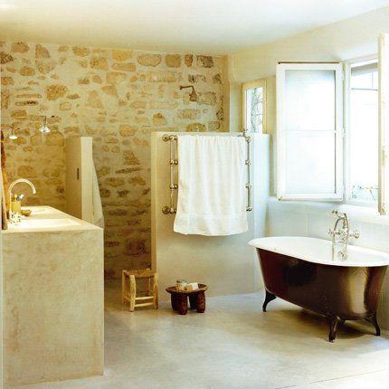 Salle de bains esprit vacances style loft avec mur en pierre et baignoire noire sur pieds