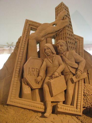 sand sculpture of a busy man and woman by Sandsational, via Flickr