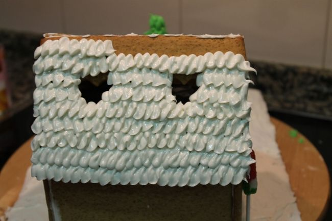decorating the gingerbread house roof with white glazing