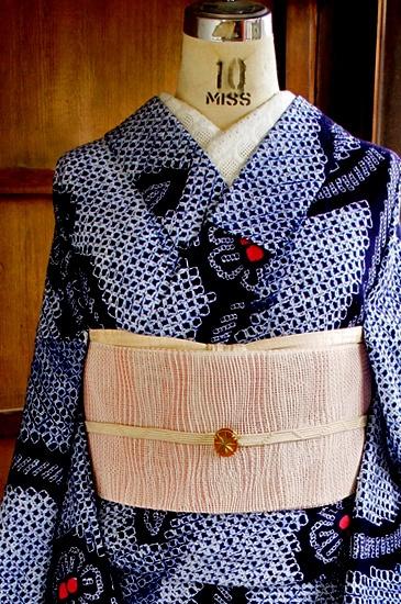 濃紺色の地に一面の匹田鹿の子絞りも風合い豊かに、ゆらぎのある優しいよろけ縞と、楚々と咲く可憐なお花模様が染め出された本絞りのレトロ浴衣です。