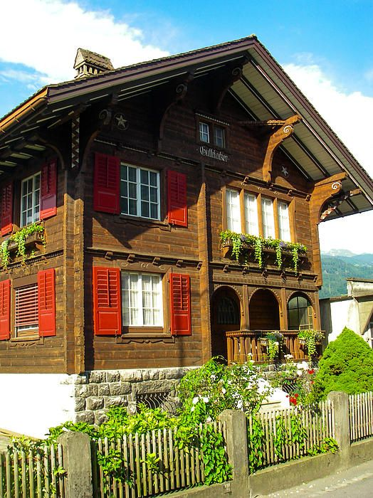 Classic Swiss Chalet and garden in spring in the Alps near the city/village of Sarganz on the border between Switzerland and Lichtenstein.. Note the beautiful red shutters on the windows and the flower boxes and balcony.
