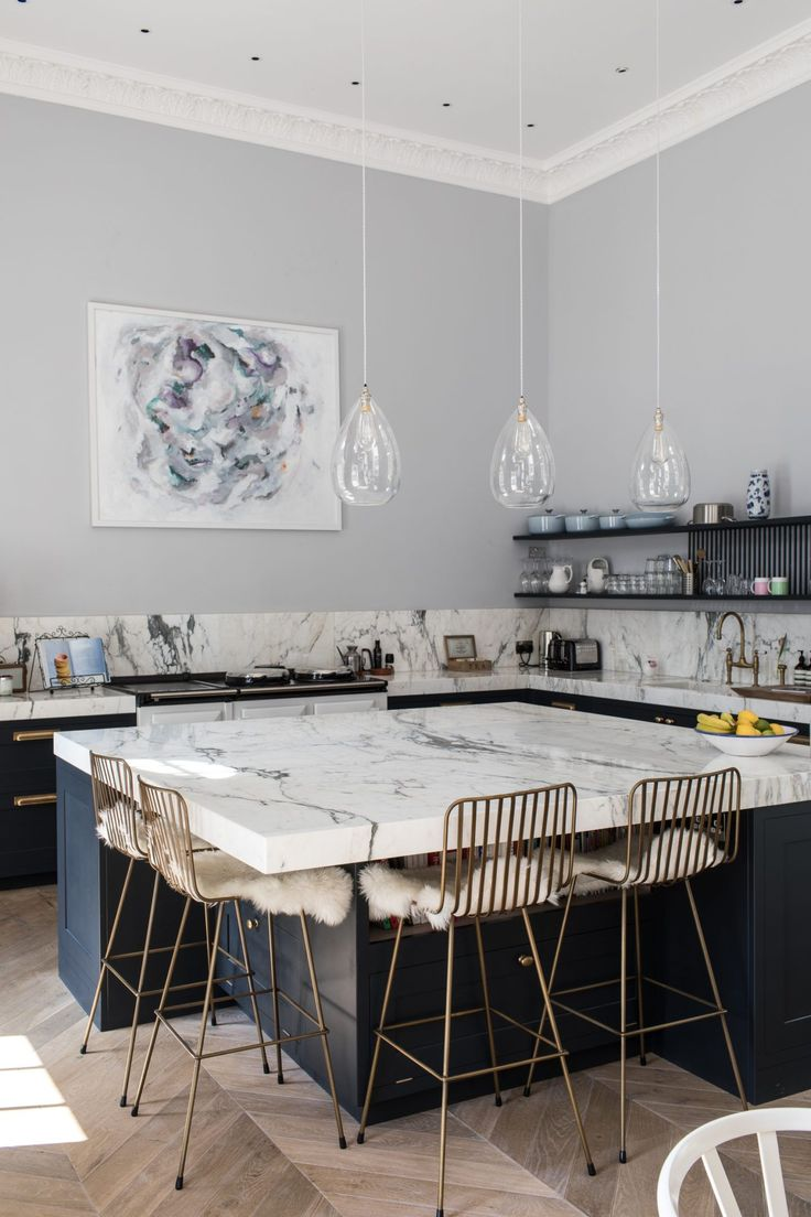 marble kitchen island + brass chairs + sheepskins + airy pendants. all good.