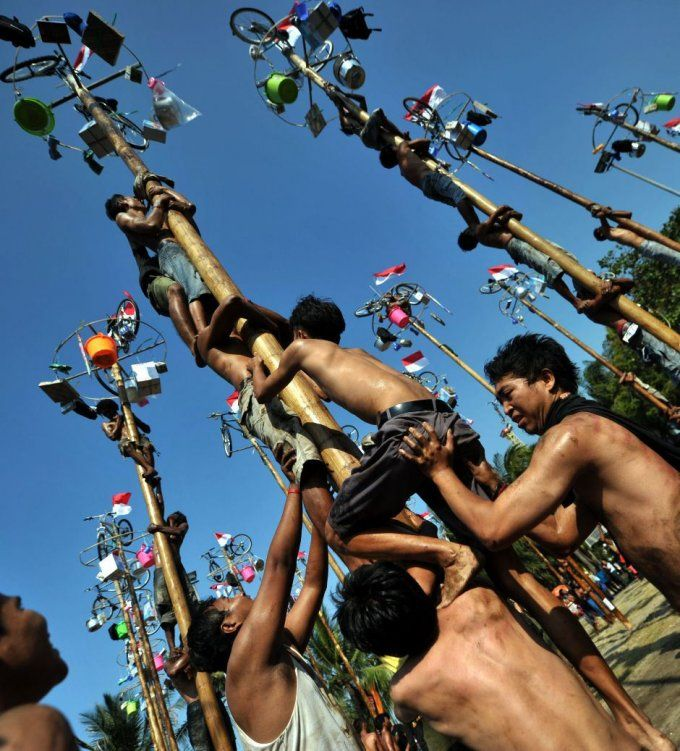Greased-pole climbers reach for the prizes during Indonesia's Independence Day celebrations | National Post