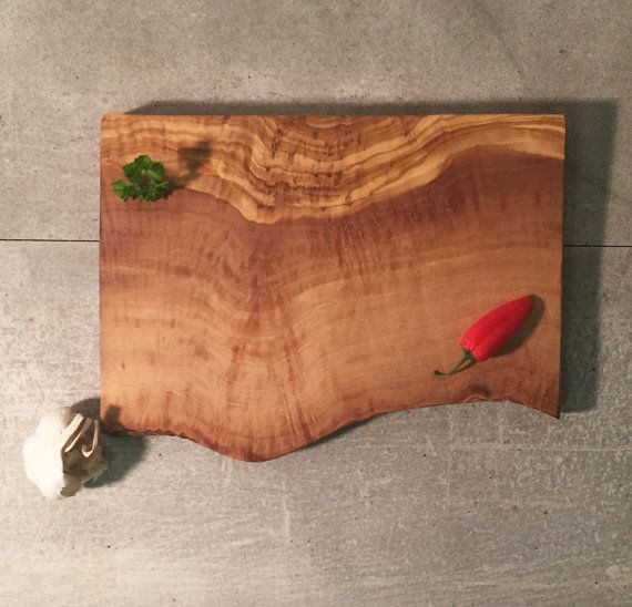 Cutting Board with Raw Edge Made From 100% Natural Olive Wood Measurements: Length approx. 10, Width variable (average 8)   This rustic cutting board is made from a single piece of solid, durable olive wood. It measures approximately 10 inches in length and features one raw edge that follows the natural structure of the olive wood tree. The solid and dense structure of the olive wood makes for an ideal cutting board but also for serving cheese and cold cuts.  As a natural result of the…