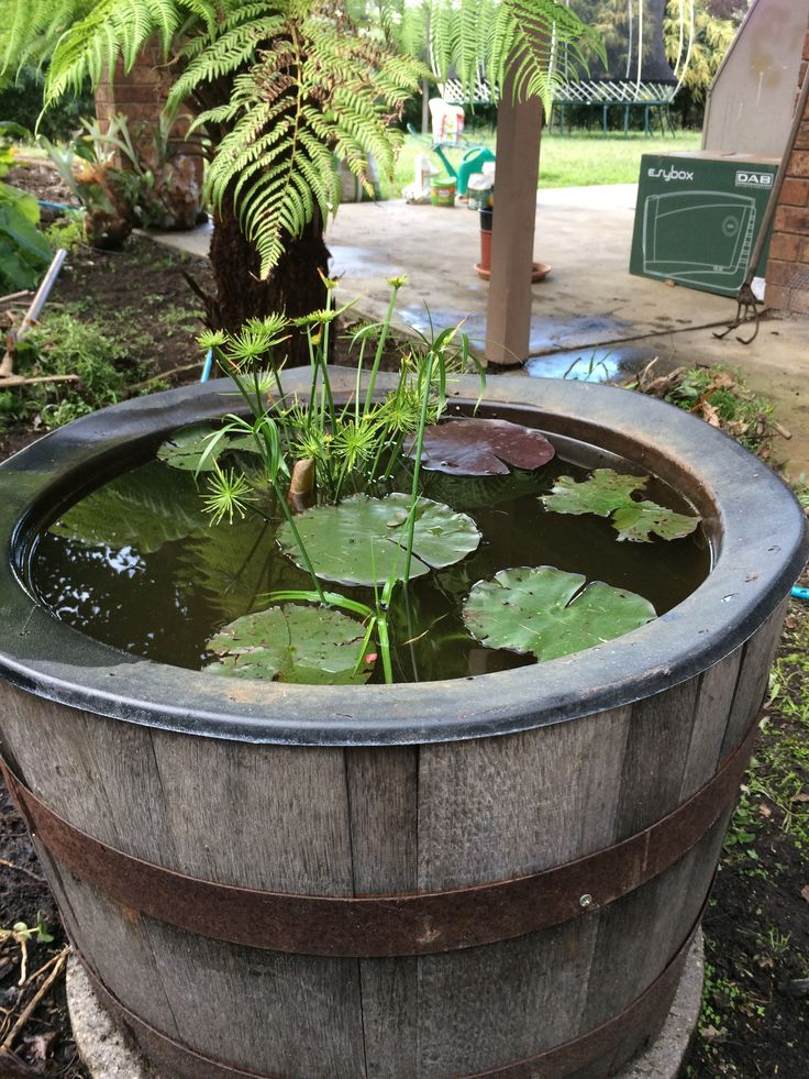 Water feature made from a half wine barrel with insert for Garden pond insert