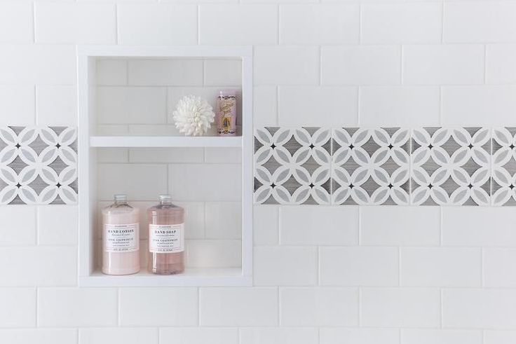 Beautiful shower is clad in white subway tiles accented with gray border tiles framing a tiled niche filled with pink bath accents.
