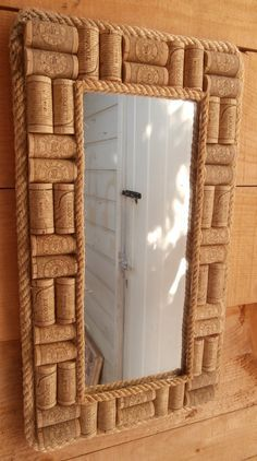 Upcycled Wine Corks Mirror - A cute little cork framed mirror which can be hung vertically or horizontally. The corks are lined up two by two.  Both the inner and outer edges have been lined with a layer of beach found rope which finish off the effect nicely.