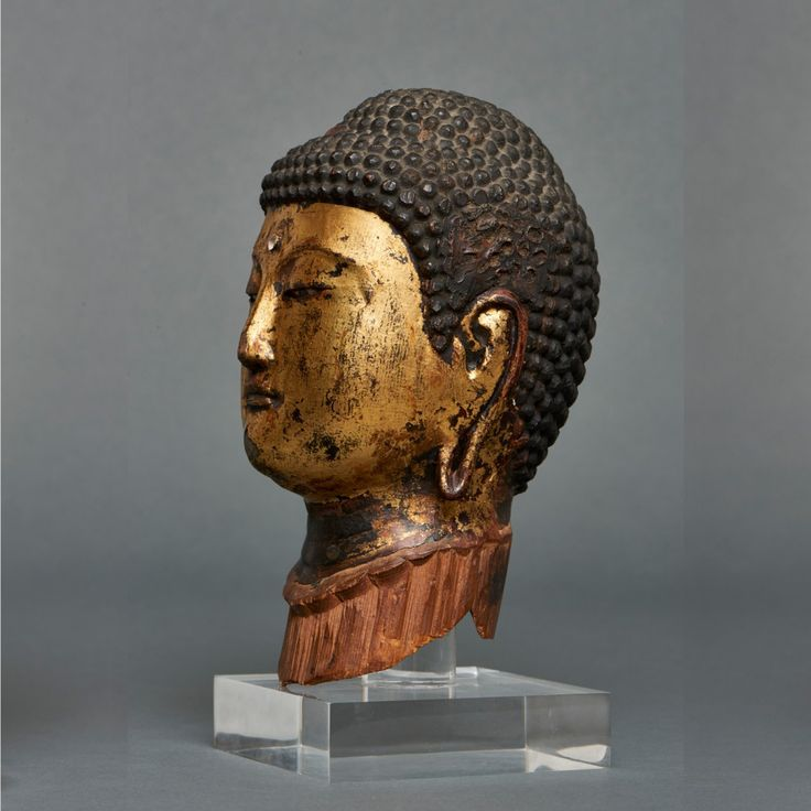 Gilded hollow head of a Buddha made from two pieces of wood. The head has inlayed eyes and crystals in the head and the forehead (ushnisha and urna) and was originally a separate head of a Buddha-figure. On a perspex stand. Kamakura Period. Size; Head H. : approx.. 20 cm; l. :approx. 11 cm. Shipping and handling…