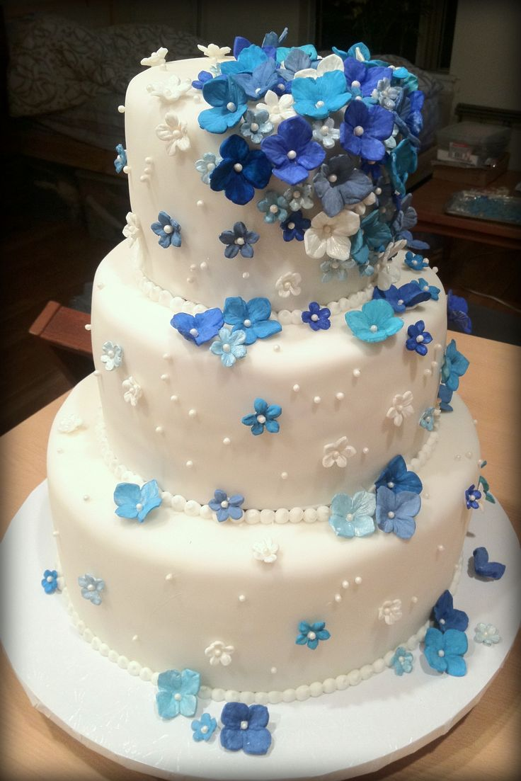 Falling hydrangeas wedding cake - White velvet butter cake with raspberry neoclassic buttercream filling and white chocolate mousseline buttercream. Covered with fondant and decorated with gumpaste hydrangeas and sugar pearls.