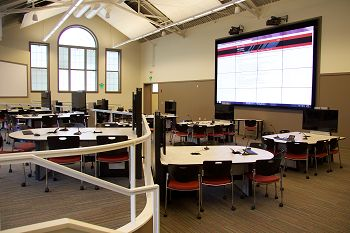 Indiana University Collaboration Studio showing group work tables and 20-foot-wide video wall for sharing work with the class.