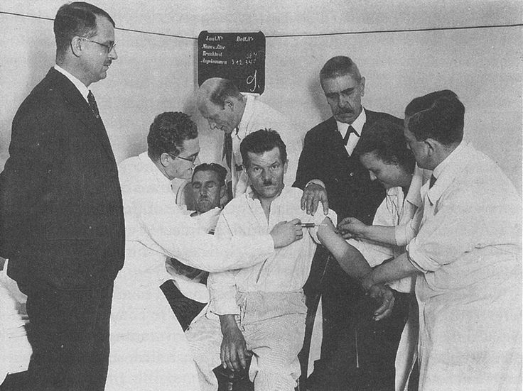 1934: Blood from a malaria patient (centre left) is injected into the arm of a psychiatric patient with general paresis of the insane (centre) which occurs in late stage syphilis. Julius Wagner-Jauregg (far left) was awarded the Nobel Prize for his discovery of this drastic but effective treatment which was utilised until the discovery of penicillin.